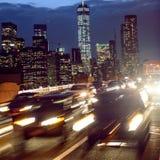Le trafic de voiture de nuit dans la rue de New York City Les gens dans l'entraînement de voitures de retour autoguident de Manha Images stock