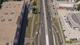 Le trafic de voiture sur la route et l'aire de stationnement dans la ville, vue aérienne en mouvement clips vidéos