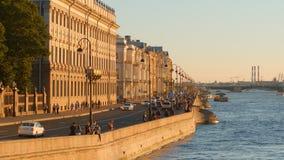 Le trafic et les personnes de voiture marchent sur le remblai de palais au coucher du soleil Images stock