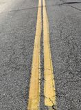 Le trafic jaune raye sur une route supérieure noire Photos libres de droits