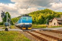Le train électrique bleu arrivant au croisement avec les barrières photos stock