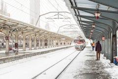 Le train arrive pendant les chutes de neige lourdes dans la gare ferroviaire de nord de Bucarest Photos stock