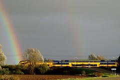 Le train courant et les arcs-en-ciel Images stock