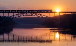 Le train de fret monte sur le pont de chemin de fer au-dessus de la rivière pendant le sunse Images libres de droits