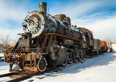 Le train de machine à vapeur sur la neige a couvert des voies images stock