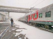 Le train de Moscou-Vladivostok est ? la station Un homme avec un enfant d?barque image stock