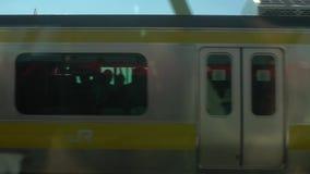Le train de mouvement lent voyage au-dessus du pont de rivière à Tokyo Gare ferroviaire Japon banque de vidéos