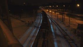 Le train de nuit va sous le pont à l'hiver