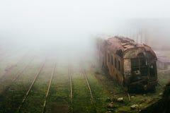 Le train de rouillement abandonné et vident des voies de train photographiées dans un jour brumeux Image stock