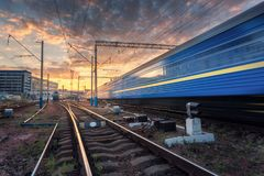 Le train de voyageurs à grande vitesse dans le mouvement sur la voie ferrée au coucher du soleil Images stock