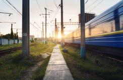 Le train de voyageurs à grande vitesse dans le mouvement sur la voie ferrée au coucher du soleil Photos libres de droits