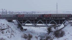 Le train de voyageurs dans le mouvement sur le pont en hiver clips vidéos