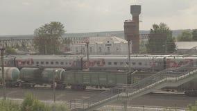 Le train de voyageurs de fond et train de fret sur la petite station Uzunovo RZD banque de vidéos