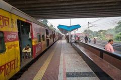 Le train de voyageurs local d'Indien environ pour quitter une gare ferroviaire un matin brumeux d'hiver Photos stock