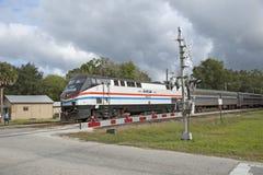 Le train de voyageurs passant la barrière Etats-Unis de passage à niveau Image libre de droits