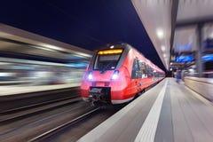 Le train de voyageurs rouge à grande vitesse moderne se déplaçant par le sta ferroviaire Image stock