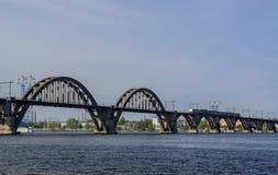 Le train de voyageurs suburbain sur le pont de Merefa-Kherson à travers la rivière de Dnieper Images stock