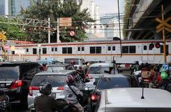 Le train fonctionne à travers la route Entraînant la voiture cesser d'attendre de ce fait entraînant des embouteillages à Jakarta photographie stock