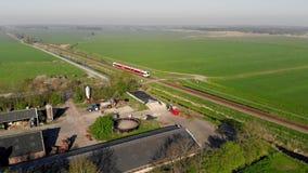 Le train interurbain de vue aérienne se déplace rapidement par les champs et le petit village clips vidéos