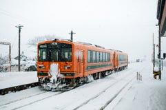 Le train orange sur la neige a couvert des voies sur le chemin de fer de Tsugaru chez Goshog Photos libres de droits