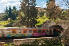 Le train passe sous le pont en pierre dans le secteur de Thiseio à Athènes Grèce Image libre de droits