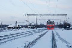Le train suit par le village russe traditionnel en hiver Photographie stock libre de droits