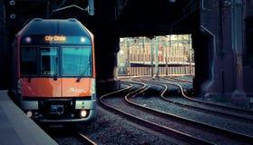 Le train a tiré dans la station au coucher du soleil images stock