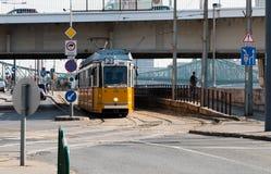 Le tram jaune monte sous le pont à Budapest Images stock