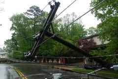 le transformateur sur un poteau et un arbre s'étendant à travers des lignes électriques au-dessus d'une route après ouragan s'est photographie stock
