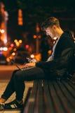 Le travail de jeune homme et communiquent la nuit Photographie stock libre de droits