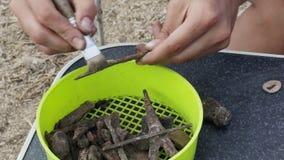 Le travail de l'archéologue sur le nettoyage primaire manuel de la découverte - une pointe de flèche rouillée banque de vidéos