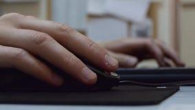 Le travail de mains masculin sur un ordinateur portable et touchent une souris noire sur une protection noire dans un bureau clips vidéos