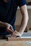 le travail de mains principal du ` s avec une surface en bois, un professionnel fait les métiers en bois Images libres de droits