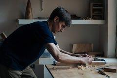 le travail de mains principal du ` s avec une surface en bois, un professionnel fait les métiers en bois Images stock