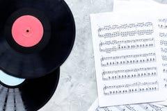 Le travail de musicien a placé avec le papier avec des notes et la vue supérieure de fond en pierre de table de vynil Image stock