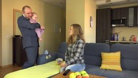 Le travail de retour de père et la babysitter d'argent de salaire pour le bébé s'inquiètent 4K banque de vidéos
