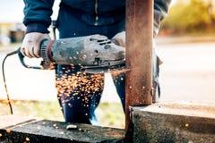 Le travailleur à l'aide de la mitre électrique de broyeur d'angle a vu pour couper la construction métallique pendant les travaux Photos stock