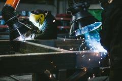 Le travailleur à l'usine dans le casque est de fer dans les RP de soudure photos stock