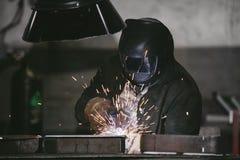 Le travailleur à l'usine dans le casque est de fer dans les RP de soudure images stock