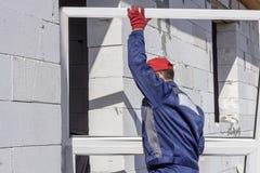 Le travailleur à la maison de chargeur de construction porte une fenêtre platic pour l'installation photos libres de droits