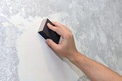 Le travailleur aligne le mur de papier sablé photos libres de droits