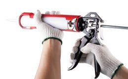 Le travailleur applique le silicone calfeutrent l'arme à feu d'isolement images libres de droits