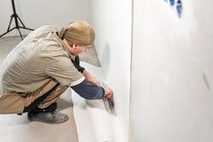 Le travailleur applique une feuille de papier peint Homme collant des papiers peints sur le mur en béton R?parez l'appartement Au photos stock