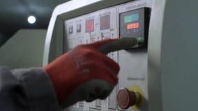 Le travailleur appuie sur le bouton sur le panneau de commande banque de vidéos