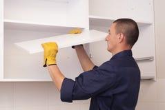 Le travailleur assemble des meubles dans la cuisine Image stock