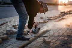 Le travailleur au chantier de construction scie des matériaux de construction photographie stock