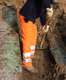 le travailleur avec l'orange halète dans le fossé Photo libre de droits
