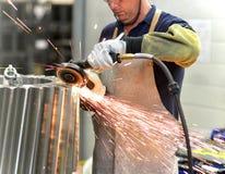 Le travailleur avec une machine de meulage traite une roue de vitesse - producti photographie stock