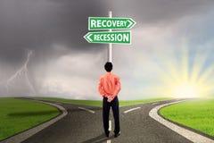 Le travailleur choisissent les finances de récession ou de relance Photographie stock libre de droits