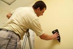 Le travailleur colle le nouveau papier peint Photo stock